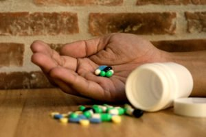 Person holding a handful of pills to represent wrongful death
